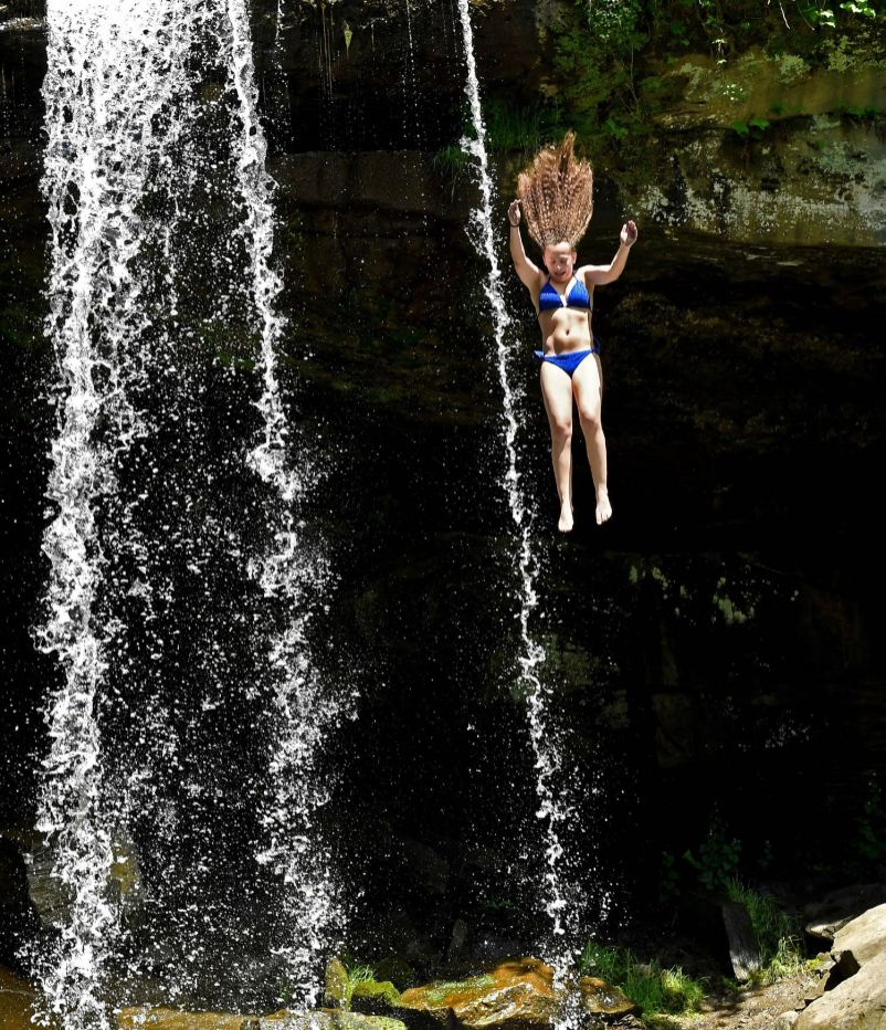 Isabella DiPietro-Harvey, 17, of the North Side, jumps off Buttermilk Falls, Tuesday, May 26, 2020, in Beaver Falls. (Matt Freed/Post-Gazette)