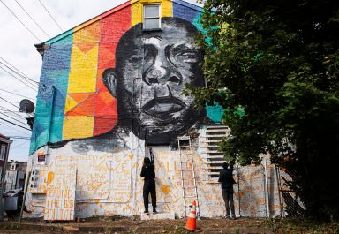 The Steelers' Terrell Edmunds, center, and Ross Marshall, right, of Windgap, paint part of a mural featuring the late civil rights leader and statesman John Lewis, Sunday, Oct. 4, 2020, in Uptown. The mural was organized by Moving the Lives of Kids Community Mural Project and Pittsburgh Solidarity for Change after Rep. Lewis' July passing at 80 years old. (Emily Matthews/Post-Gazette)
