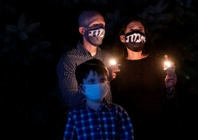 """Jordan Fischbach, left, Yael Silk, right, and Nathaniel Fischbach, 8, hold candles as they participate in a Havdalah service to honor the memory of Supreme Court Justice Ruth Bader Ginsburg, Saturday, Sept. 26, 2020, outside Sixth Presbyterian Church in their neighborhood of Squirrel Hill. """"It's on all of us to pursue justice in her stead,"""" said Teddi Horvitz, president of the National Council of Jewish Women Pittsburgh, who opened the event with her remarks. (Emily Matthews/Post-Gazette)"""