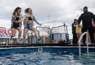 Anna Franksain, left, and Emily Bishop, both 18-year-old seniors at Mars Area High School, leap into a pool of water at the 2020 Pittsburgh Polar Plunge & Festival, Friday, Feb. 28, 2020, at Heinz Field on the North Shore. About 500 students and teachers from several local schools took part in the event to benefit Special Olympics Pennsylvania. (Steve Mellon/Post-Gazette)