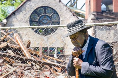 "Pastor Frank Tillman Junior pauses by the collapsed Christian Fellowship Center and the Church of God in Christ, Friday, Jun 12, 2020, in Woods Run. The church did not have enough income to replace the entire roof on the building, which had been upright since 1861 and an ""acting force"" in the Underground Railroad, according to Mr. Tillman. (Pam Panchak/Post-Gazette)"