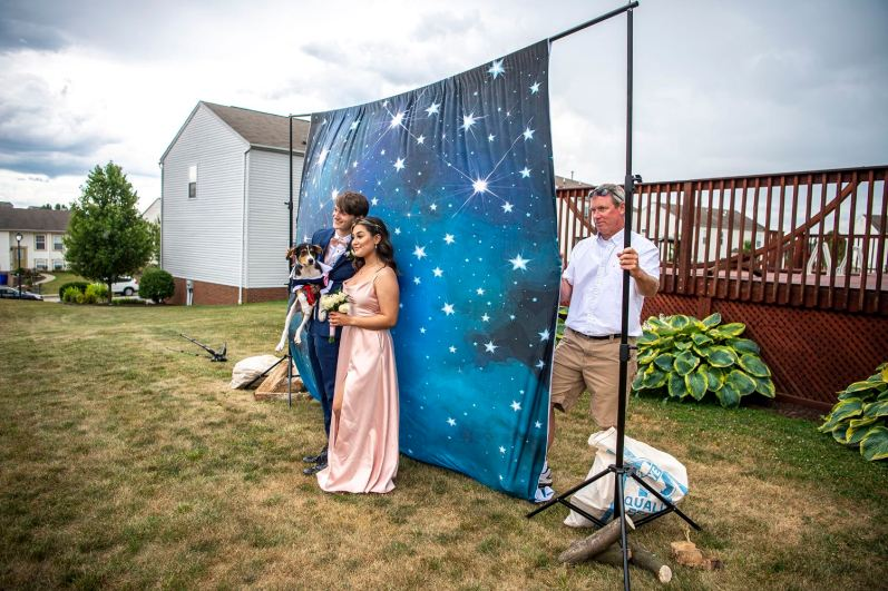 "Ryan Painter, left, a recent graduate, Sky Miller, a rising senior, and Mr. Painter's dog Root Beer pose for a photo in front of a backdrop during a backyard ""prom"" for West Allegheny High School students, Thursday, June 25, 2020, in McDonald. After the school's official prom was canceled due to the COVID-19 pandemic, the family of senior Alex Morrison decided to host a prom on their nearly one acre of property. (Alexandra Wimley/Post-Gazette)"