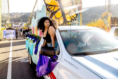 "An organizer leans out of a decorated truck leading hundreds on a march on the 10th Street Bridge from the South Side to Downtown during a ""Every Voice Heard, Every Vote Counted"" event to call for an accurate count of votes in Pennsylvania and to celebrate Joe Biden winning the presidency, Saturday, Nov. 7, 2020. (Alexandra Wimley/Post-Gazette)"