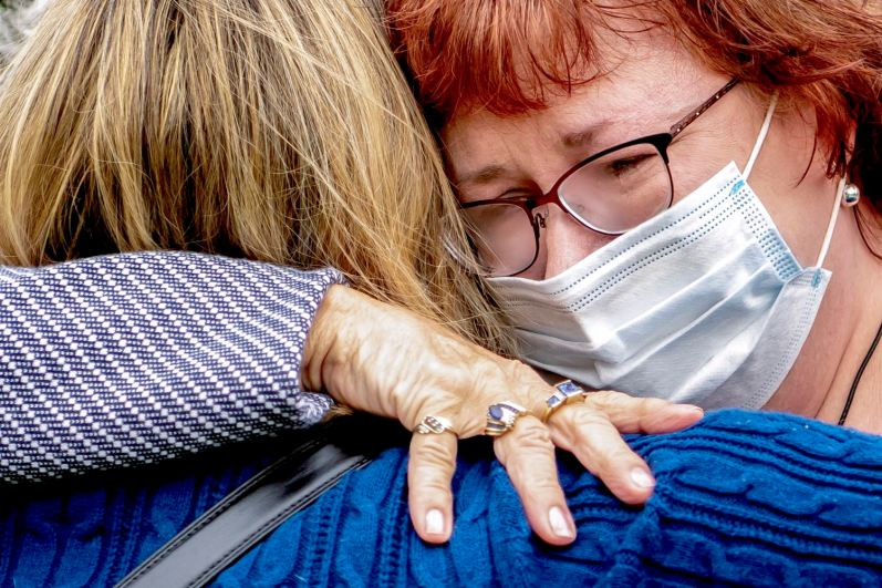 Kristie Park of Baden, left, comforts her friend Jodi Gill, whose father Glenn Gill contracted COVID-19 while a resident at Brighton Rehabilitation and Wellness Center, Wednesday, Oct. 21, 2020, in Beaver. The two were at a press conference about a lawsuit filed against the nursing home, which was host to one of the worst COVID-19 outbreaks in the country. (Alexandra Wimley/Post-Gazette)