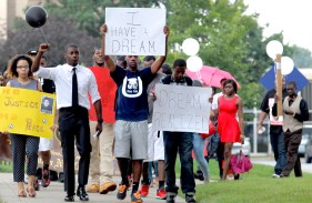 Marchers, including Black Student Union members Robert Delk, front left, Robert Tift and Domonick Powell, carry signs and balloons throughout the University of Toledo during a MLK march and to reflect on the trial over the death of Trayvon Martin. The Blade/Lori King
