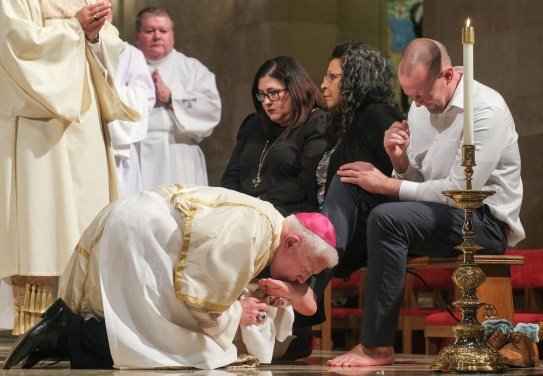 Bishop Daniel E. Thomas washes the feet of RCIA candidate Eddie Knight of Toledo during the Thursday of the Lord's Supper Mass Thursday, April 18, 2019, at the Rosary Cathedral in Toledo, Ohio. THE BLADE/JEREMY WADSWORTH CTY mass19