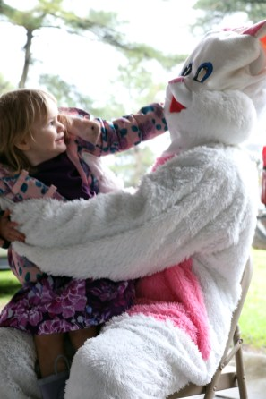 """Lilliana Swearingen, 2, pulls on the Easter Bunny's ear while sitting on his lap for a picture during the 5th annual """"Eggstravaganza 2019"""" sponsored by the nonprofit Holiday Angels Toledo in Walbridge Park on Sunday, April 14, 2019. THE BLADE/AMY E. VOIGT CTY roveasterparty"""
