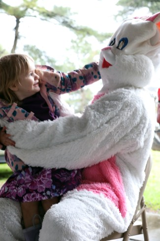 "Lilliana Swearingen, 2, pulls on the Easter Bunny's ear while sitting on his lap for a picture during the 5th annual ""Eggstravaganza 2019"" sponsored by the nonprofit Holiday Angels Toledo in Walbridge Park on Sunday, April 14, 2019. THE BLADE/AMY E. VOIGT CTY roveasterparty"