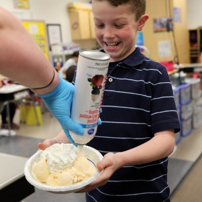 Third grader Calvin Marko watches as Toledo Police Officer Emily Myles sprays whipped cream on his ice cream during an ice cream party provided by the Toledo Police Department at Elmhurst Elementary School Wednesday, May 22, 2019 in Toledo. The class, along with a class at at Glendale-Feilbach Elementary School, came up with the name, 'Cops and Cones,' for the police department's ice cream truck which will hit the streets early this summer. THE BLADE/DAVE ZAPOTOSKY