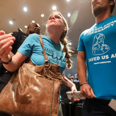 Anti-abortion activists Melissa Kasza, left, and Joe Boggs yell at city council members while being escorted out after the city council voted to condemn the heartbeat bill at the One Government Center in Toledo, Ohio on Wednesday June 26, 2019. THE BLADE/REBECCA BENSON