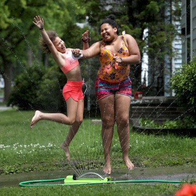 Quinn Glanz, left, and Olivia Ward, both 10, play in a sprinkler at Ward's Hagley Rd. home in Toledo on Wednesday, June 12, 2019. THE BLADE/LORI KING