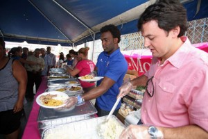 T-Mobile Puerto Rico General Manager Jorge Martel (right) and Olympian Jaime Espinal (center) help dish out meals during the company's traditional Christmas lunch at La Fondita de Jesús.