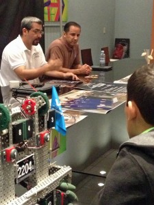 From left: Wence López, president of PRIOR, Astronaut Joseph Acaba and a student with his robot discuss this weekend's competiton Tuesday.