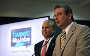 Gov. Alejandro García-Padilla discusses the details of the TweetMyJobs platform as Economic Development and Commerce Secretary Alberto Bacó stands by.
