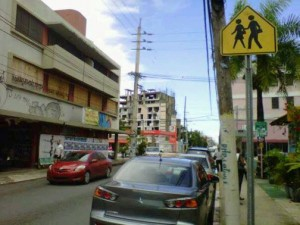 Prominent examples of urban decay on Loíza street are the two buildings on the left: one a two-story commercial structure that most recently housed an art gallery/frameshop and the other, in the background, a condominium abandoned in mid-construction more than a decade ago.