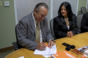 Manuel Cidre signs the collaborative agreement earlier this month in Orlando, as a member of that city's Hispanic Chamber of Commerce looks on.