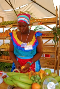 Angelina Kassiany, dressed in colorful costume, cuts fruits at a Proexport produce stand at the convention center in Cartagena, Colombia. (Credit: Larry Luxner)