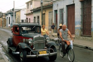Bicyclists ride past an ancient Chevrolet on the streets of Camagüey, Cuba. (Credit: Larry Luxner)