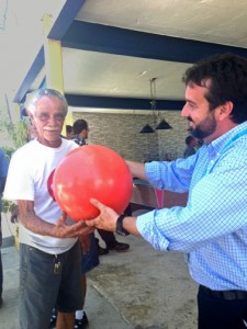 Jaime Pabón, Aerostar's environmental director (right), hands a buoy to fisherman Armengot Rivera.