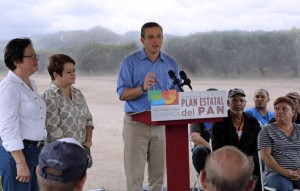 Gov. García-Padilla, at podium, explains the changes, while Agriculture Secretary Myrna Comas (left) and Family Department Secretary Idalia Colón listen.