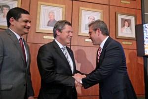 Gov. García-Padilla shakes hands with Lufthansa Technick President Elmar Lutter, as UPR President Uroyoán Walker looks on.