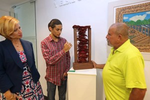 "Hamid Burgos, winner in the sculpture category, from the Luis Llorens Torres School in Juana Díaz, explained the details of his work ""Fosa Común"" to Carmen Pagán, first vice president of compliance and community reinvestment at FirstBank, and Melquiades Rosario-Sastre , director of the Fundación Proyecto La Línea de mi Pensamiento."