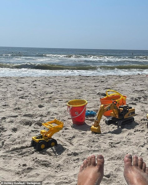 Mom life: In another photo we see Ashley's feet as her son's toys sit in the sand inches away