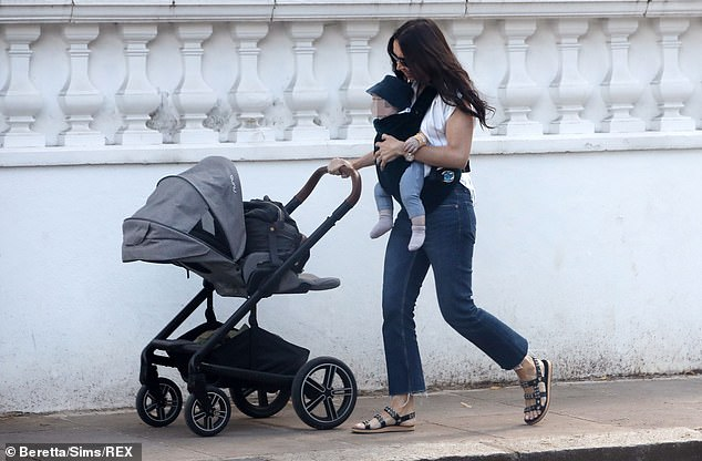 Effortless: The  TV presenter looked effortlessly stylish on her mother-son walk, donning a blue mom jeans and white striped-shirt combo
