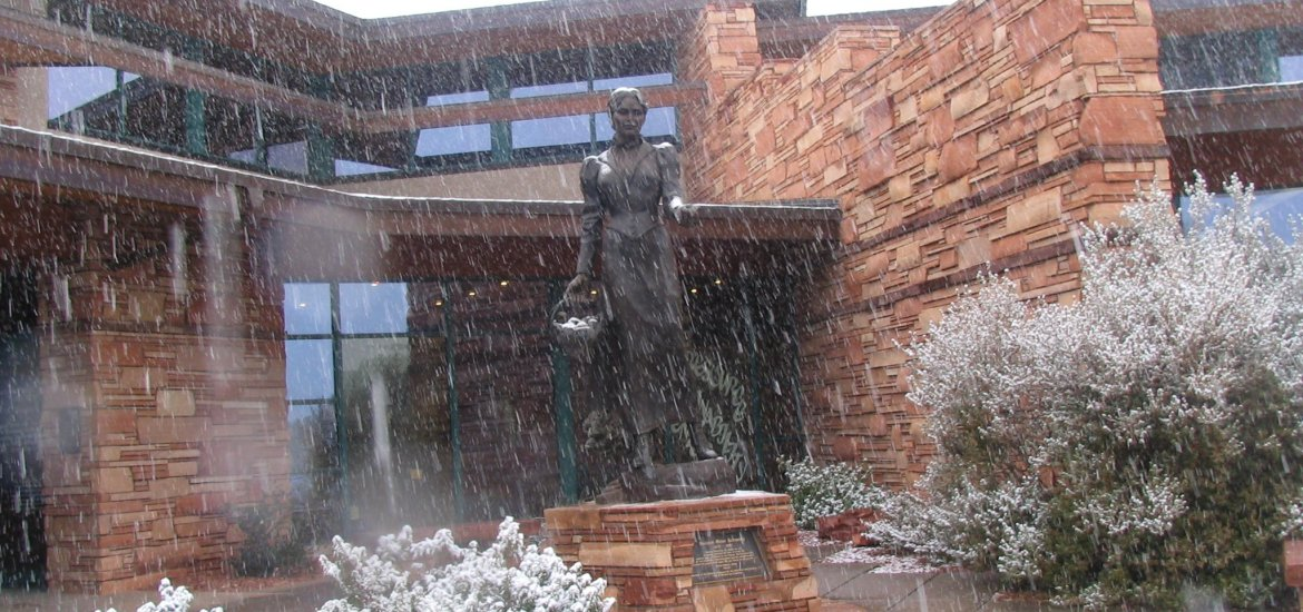 The Sedona Schnebly statue stands near the entrance of the Library, in the snow.