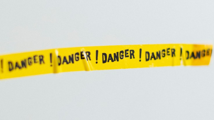 """Yellow tape with the word """"danger"""" repeated on it"""