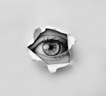 eye peeking through hole in paper