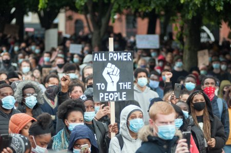 """Crowd of people at a Black Lives Matter Protest with a sign reading: Power to the People"""""""