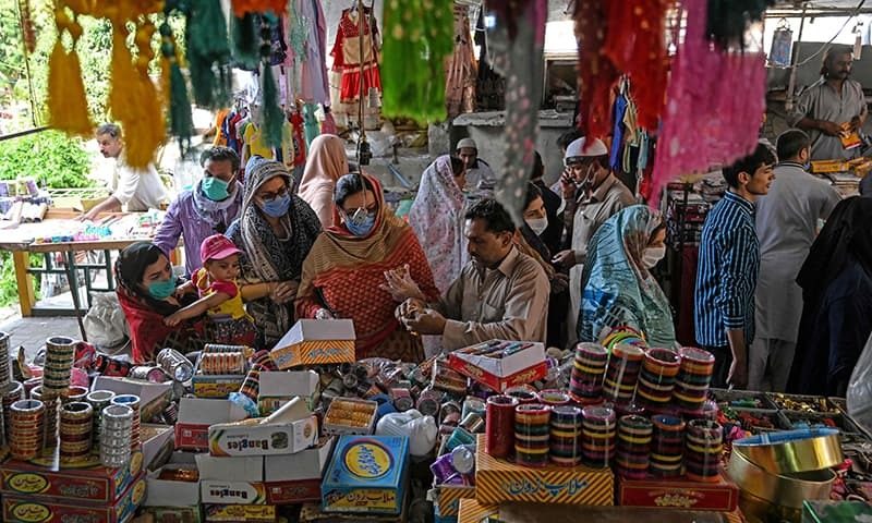 Customers shop for bangles at a market in Islamabad on May 9. — AFP