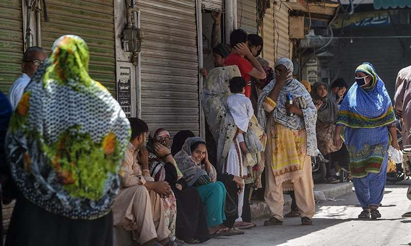 People gather as they wait for the reopening of shops in Lahore on Saturday. — AFP