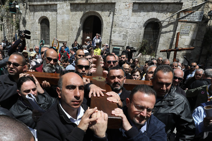 Members of a local Catholic Palestinian parish carry a wooden cross along the Via Dolorosa (Way of Suffering) in Jerusalem's