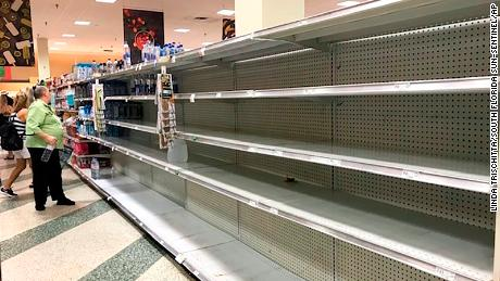 Shoppers look at empty shelves as large jugs of water are sold out at a supermarket after the water main break in Fort Lauderdale.