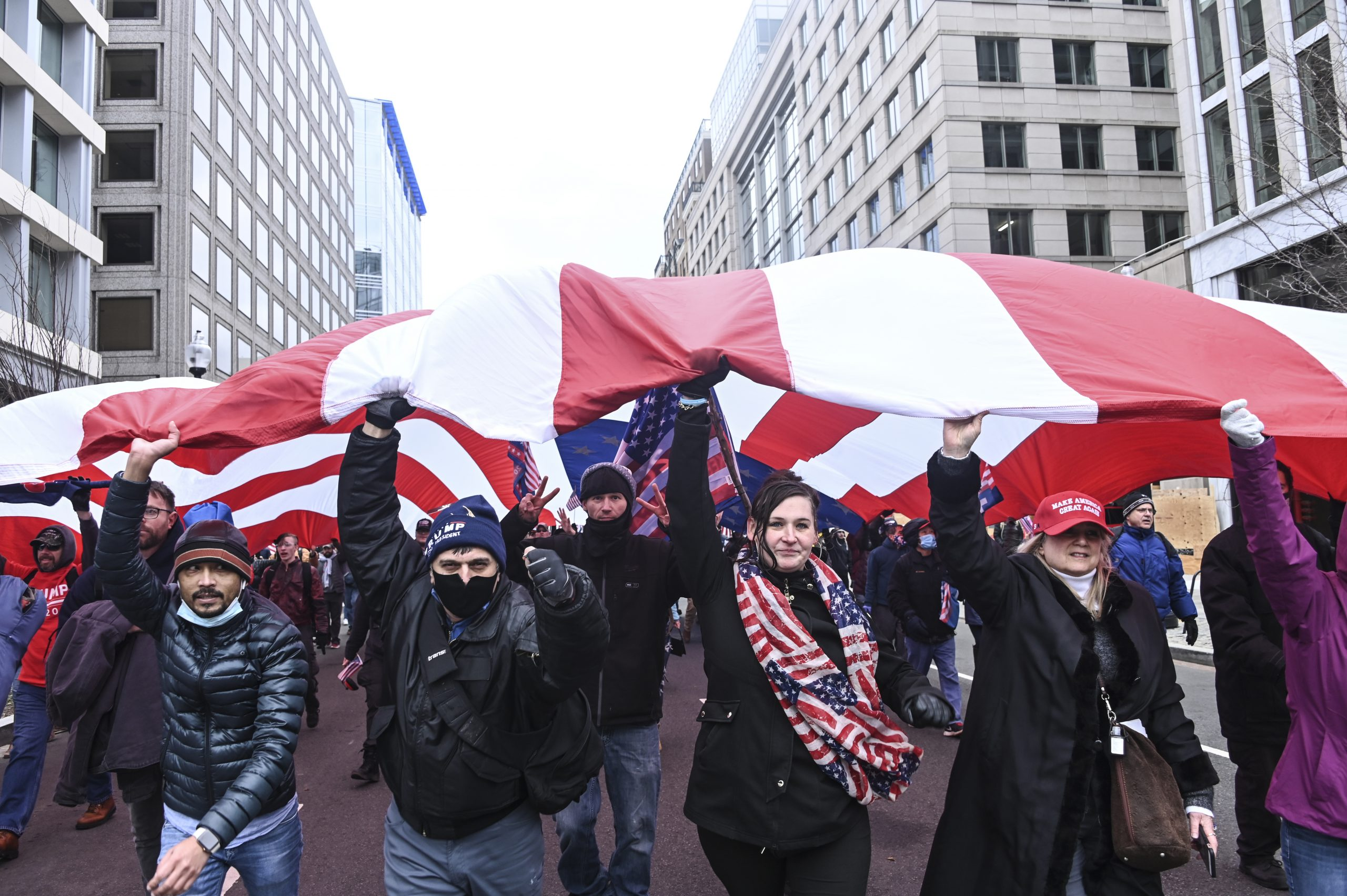 Trump supporters march with a massive American flag in front of Black Lives Matter Plaza.