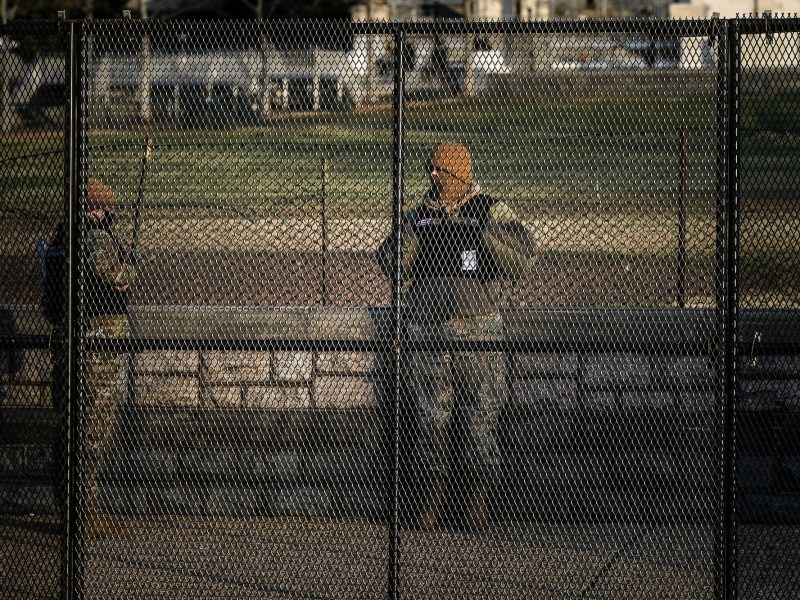 Law enforcement officer behind a security fence