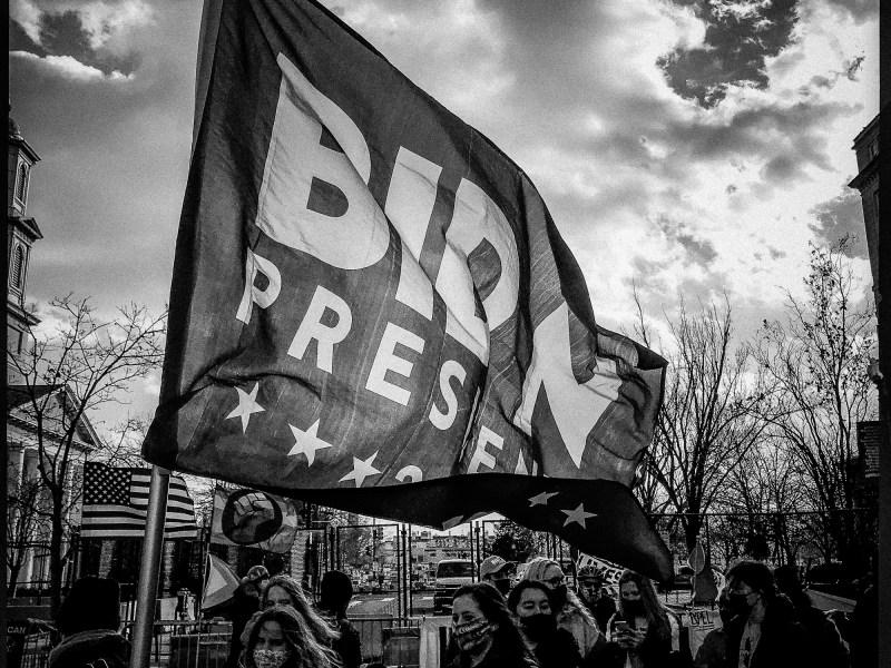 Woman holding flag supporting Joe Biden