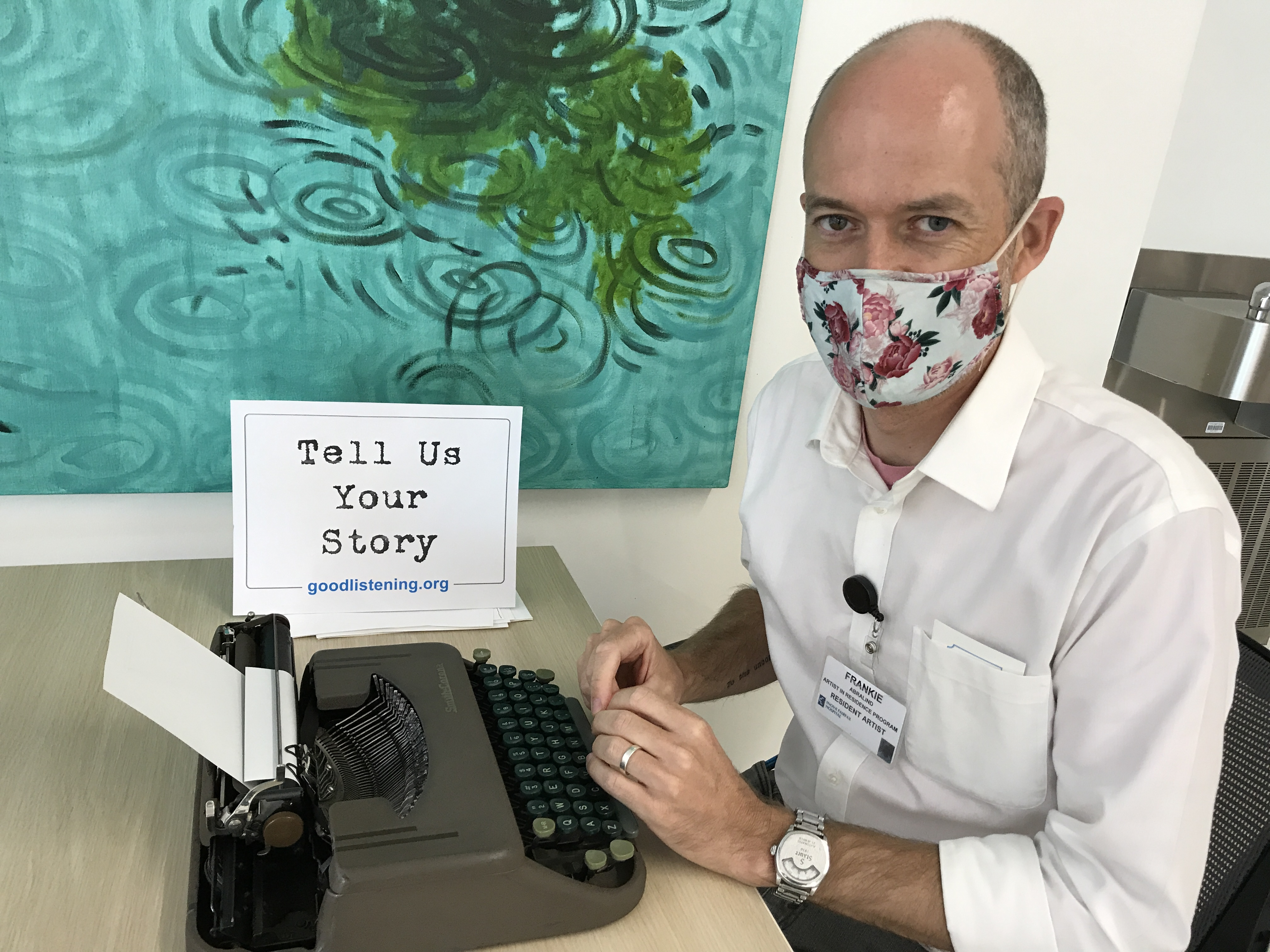 """Frankie Abralind in front of a typwriter and a The Good Listening Project sign that says """"Tell Us Your Story."""""""