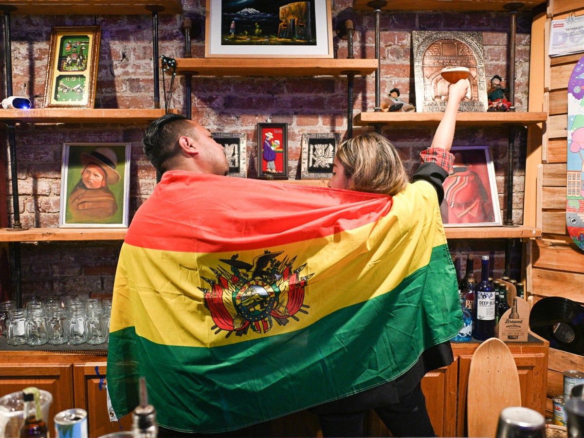 Casa Kantuta founders Carla and Juan Sanchez holding a Bolivian flag