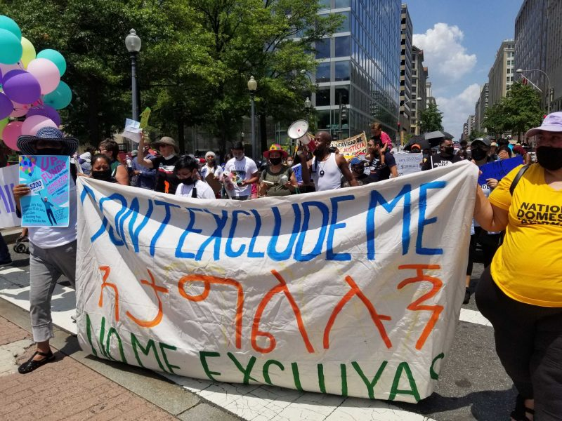 """excluded workers carry a sign saying """"don't exclude me"""" in english, amharic, and spanish"""