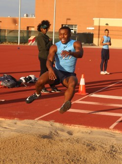 Senior Jabari Aiken braces for impact from his long jump. Photo by Liberty Vela.