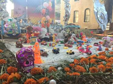 Lainer High School art club make an ofenda honoring children who have passed away in detention centers, featuring a fence, toys, and mural in the background.