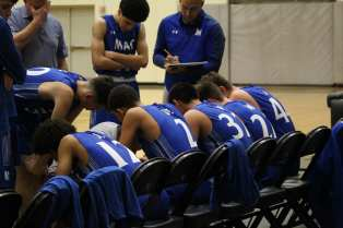 The team (left to right) Leander Thompson, Caleb Gaston, Anthony Reyes, Michael Howard, and Garrett Prince talking strategies during after the third quarter with Madison in the lead 34-15.