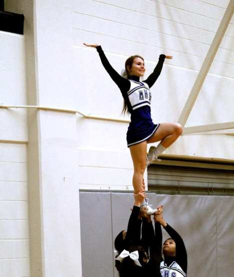 Cheerleader Kirsten Rivera waving to the crowd after the first quarter.