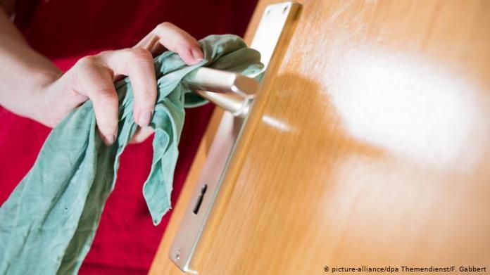 Human hand cleaning a door handle