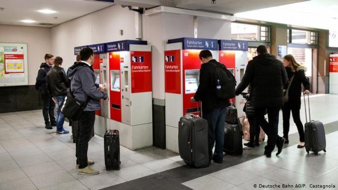 People buying train tickets at vending machines (Deutsche Bahn AG / P. Castagnola)