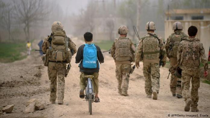 An Afghan boy with an UNICEF schoolbag rides his bicycle past German Soldiers as patrol the area near the DHQ (Char Dara District Police Headquarter) in the province of Kunduz on March 29, 2012