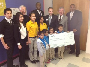 CEO Doyle Beneby and Board Chairman Derrick Howard present a grant to KIPP Academy as part of the New Energy Economy